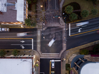 View from above of traffic intersection with motion blur cars turning.