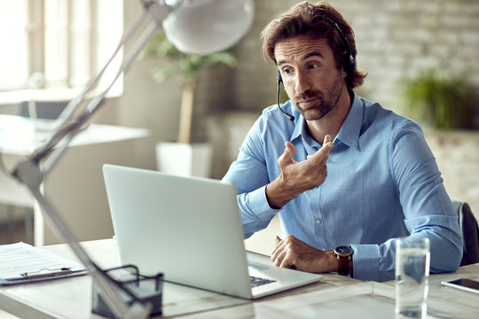 Businessman having online meeting over laptop while working in the office.