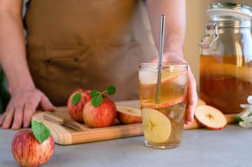 A man in an apron preparing a drink kombucha iced tea. Fermented probiotic refreshing kombucha or apple cider in a glass. Horizontal orientation.