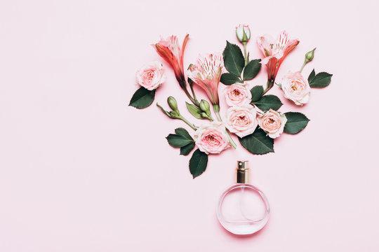 Bottle of perfume and flower arrangement of rosebuds on pink background