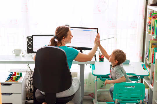 Mother with kid working from home during quarantine. Stay at home, work from home concept during coronavirus pandemic