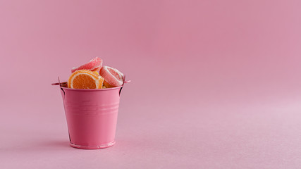 Full of colourful fruit Jelly candy in a pink bucket against pink background for food and snack concept