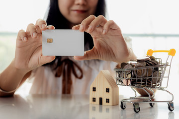 Selective focus of hand holding a blank credit chip card with wooden house model and full of coins in shopping cart for planning, savings and property investment concept