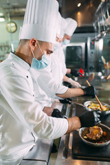Chefs in protective masks and gloves prepare food in the kitchen of a restaurant or hotel.