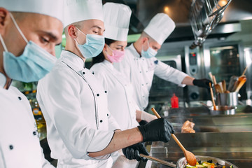 Photo sur cadre textile Pain Chefs in protective masks and gloves prepare food in the kitchen of a restaurant or hotel.