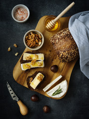 Breakfast concept. Freshly baked bread, Camembert cheese, honey and walnuts.