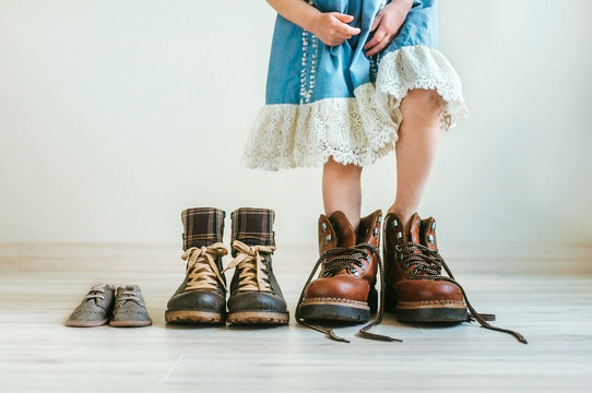 Close up of little girl in  dress putting on fathers hiking shoes