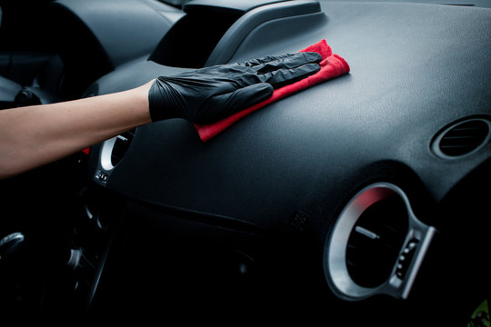 Technician with gloves cleaning the car dashboard with red cloth. Topical car wash and care. protection of the interior of the automobile. cleaning, health and care concept.