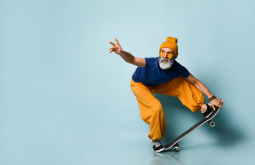 Gray-bearded grandpa in t-shirt, sunglasses, orange pants, hat, gumshoes. Riding black skateboard, posing on blue background