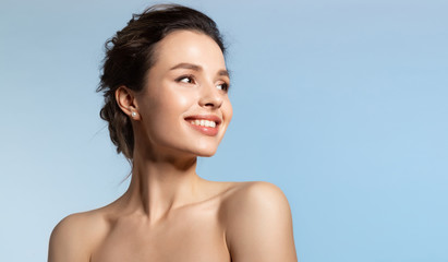 Toothy smiling young woman with shiny glowing perfect facial skin and bare shoulder looking aside.