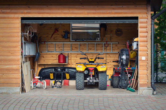 Facade front view open door ATV quad bike motorcycle parking messy garage building with wooden siding at home driveway backyard and lawn path. House warehouse for tools and equipment . Garage sale