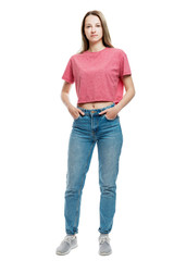 A young girl in jeans and a red T-shirt stands holding hands in pockets. Full height. Isolated on a white background. Vertical.