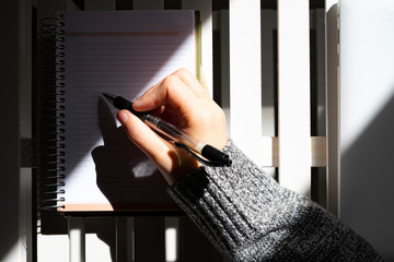 Woman writing on her calendar with a black pen.