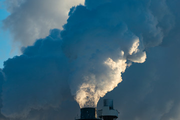 Smoke Stacks Pour Pollution Backlit by Sunrise