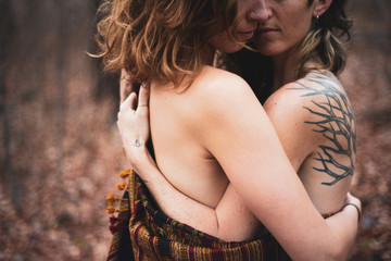 artistic faceless portrait of female gay couple hugging in woods