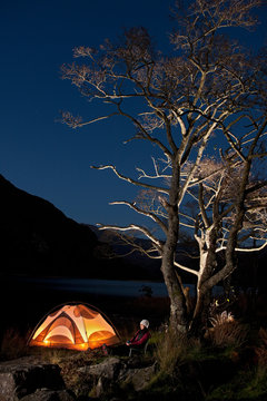 female hiker sitting outside her tent at camp in North Wales