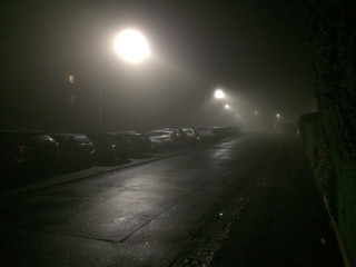Cars In Parking Lot By Illuminated Empty Road At Night