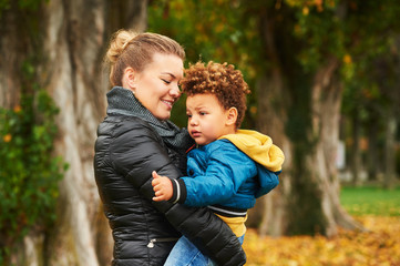Happy young mother holding sweet toddler boy family having fun together outside on a nice autumn day