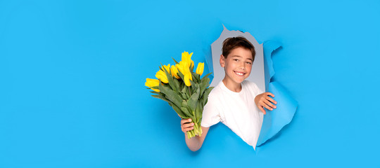 Smiling child boy with bouquet of yellow tulip flowers.
