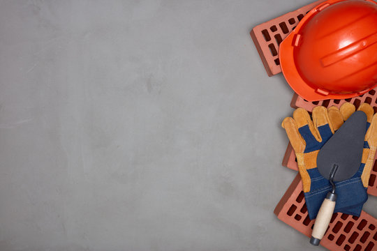 Stack of bricks with masonry trowel, construction hard hat, gloves on gray concrete background. Top view. Construction concept.