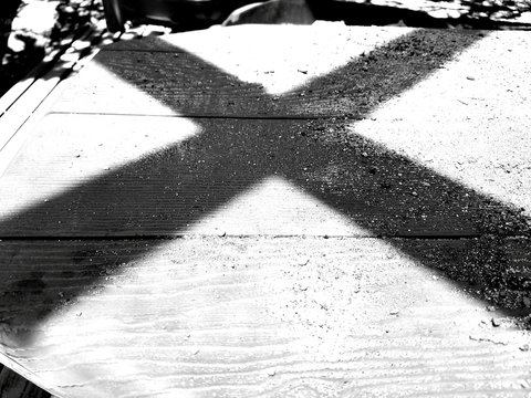 Shadow On Letter X On Boardwalk During Sunny Day