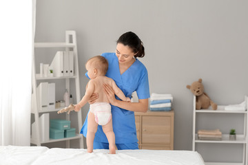 Massage therapist working with cute baby in medical center