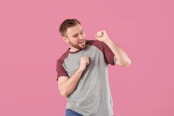 Handsome dancing man on color background
