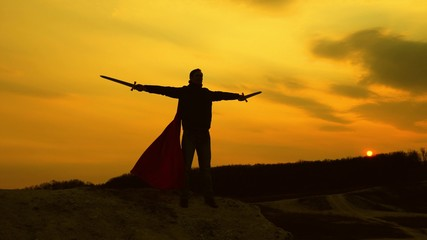 a warrior with sword in his hand and in red cloak stands on mountain in sunset light. free male knight prays with swords outstretched hands. free man plays superhero. game of Roman legion.