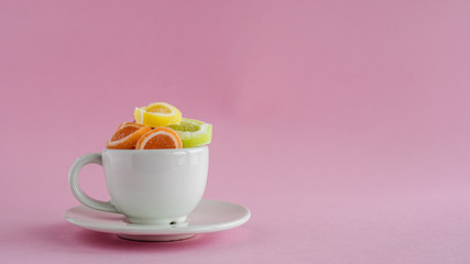 Colourful fruit Jelly candy in a white coffee cup against pink background for food and snack concept