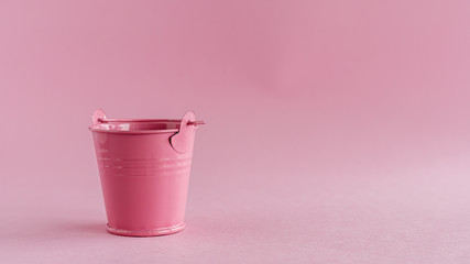 Mini colored tin pail or bucket on pink background with copy space for household items concept