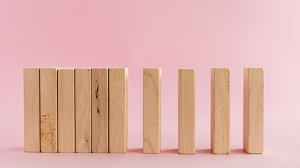 Wooden toys arranged in a horizontal row on pink background for leisure activities concept