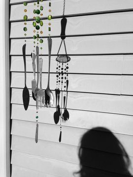Cutlery Wind Chime Hanging Against Blinds