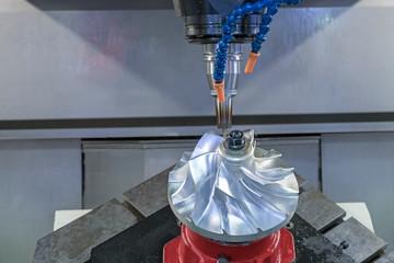 Fototapeta Five axis CNC machining center cutting jet engine turbine.