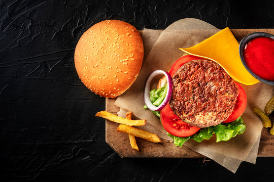 Burger with beef, cheese, onion, tomato, and green salad, with a bun and ketchup, with French fries, shot from the top on a black background with a place for text