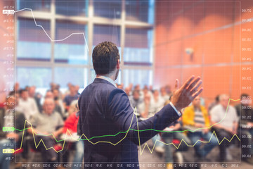 Wall Mural - Speaker at business conference with public presentations. Audience at the conference hall. Trough the transparent presentation screen view. Chart can be seen in forground.