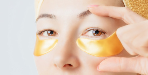 Young woman applying golden under eye hydrogel patch, close-up.
