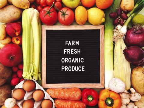 Farm fresh organic produce sign against a rustic background of fresh fruit and vegetables. Farmers market ingredients. Locally sourced, organic and healthy veggies. Concept message board