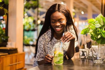 African Woman drinking lemonade with a straw, in a restaurant