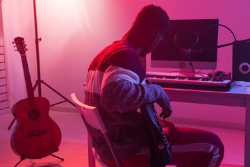 Create music and a recording studio concept - African american man guitarist recording electric bass guitar track in home studio