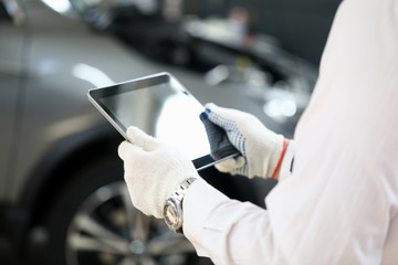 Man holds tablet near car for troubleshooting