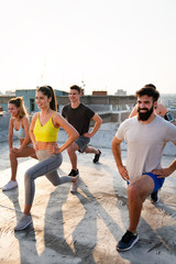 Fitness, sport, training and lifestyle concept. Group of fit people exercising outdoor