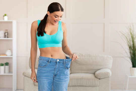 Excited Woman Wearing Too Big Jeans After Weight-Loss At Home