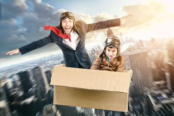 Father and son flying in a cardboard box