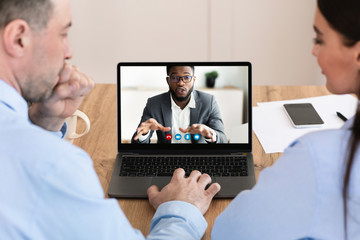 Workers having discussion during video call with colleague