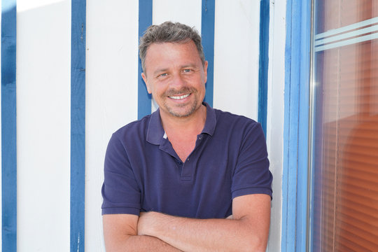 Outdoor happy handsome man arms crossed in white blue wooden hut background in arcachon bassin France