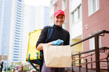 delivery, mail and people concept - happy man delivering food in disposable paper bag to customer...