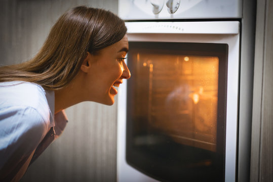 Cheerful young woman looking into oven showcase at kitchen