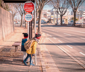 Two Japanese kids is waiting for school bus at Bus stop.