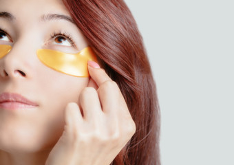 Young woman applying hydrogel golden patch under eye.