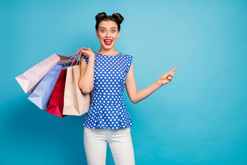 Photo of pretty excited lady hold many packs addicted shopaholic indicating finger empty space advising low prices wear dotted blouse white pants isolated blue color background